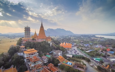 Aerial view scenery of Wat Tham Khao Noi and Wat Tham Sua on top hill, chinese shrine monastery with paddy rice field and sun rays in the sky background, Tha Muang District, Kanchanaburi, Thailand.