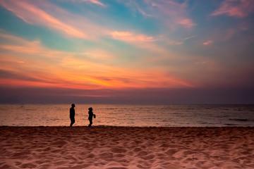 silhouette couple walking on beach, sun set, twilight, copy space