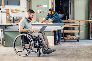 worker in wheelchair with computer in a carpenter's workshop with his colleagu