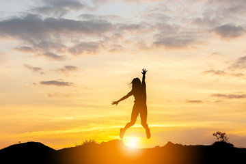 Silhouette of a Happy young woman jumping at the sunset, Freedom and enjoyment concept.