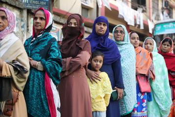 Female voters with children stand in a queue at a voting center to cast their vote during the general election in Dhaka