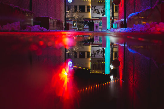 Down on the wet frozen alleyway in the night light and the red glowing lights.