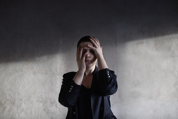 Girl with short haircut hides her face with hands