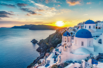 Spoed Fotobehang Beige Beautiful view of Churches in Oia village, Santorini island in Greece at sunset, with dramatic sky.