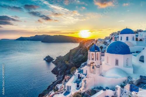 Fototapete Beautiful view of Churches in Oia village, Santorini island in Greece at sunset, with dramatic sky.