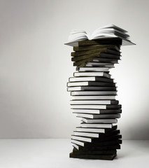A spiral of stacks of books in the form of DNA and an open textbook at the top.