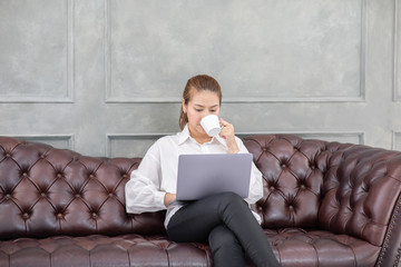 Beautiful Attractive Asian business woman sitting on sofa drinking coffee and using computer laptop to reading news and checking her work on e-mail in the morning in living room and work from home