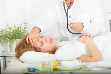 Medical doctor touching patient's forehead checkong for temperature and fever