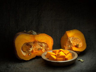Acorn winter squash, pumpkin, prepared for cooking, cubes with seeds. Life cycle concept. Chiaroscuro, baroque style light painting.