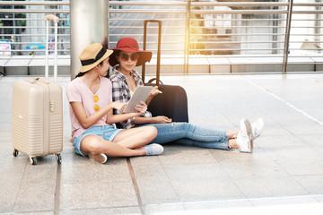 Two beautiful tourists stand talking map.