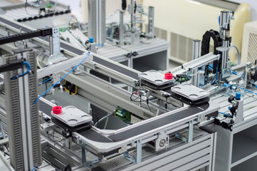 Gripper picks up the product from automated car which is on the manufacturing line in a smart factory. Industry 4.0 concept; artificial intelligence in manufacturing.