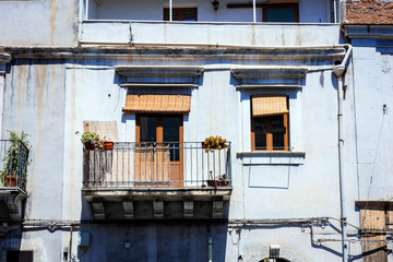 Balcony in a historic building in Catania, traditional architecture of Sicily, Italy.
