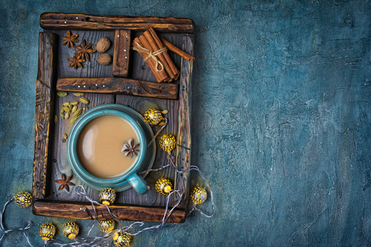 Masala chai tea with milk and spices in vintage wooden box and Christmas lighted garland