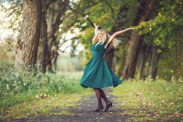 a blonde girl in a green long dress is spinning around an oak grove