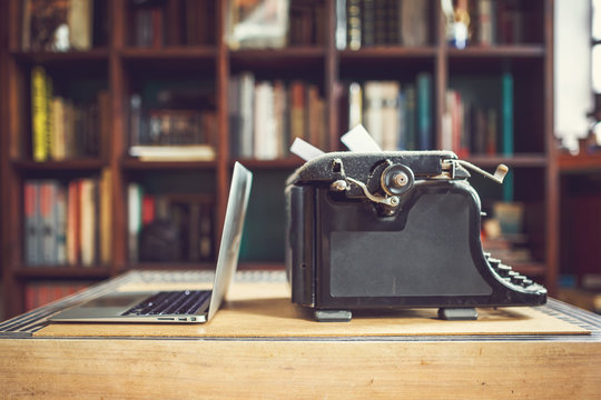old vintage dust-covered typewriter with sheet of white paper near modern notebook on bookcase background. modern technology and vintage appliances