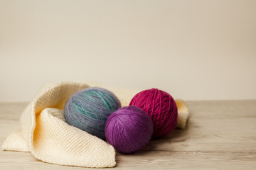 Balls of thread for knitting on a wooden background