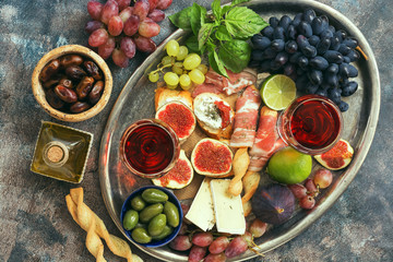 Appetizers table with italian antipasti snacks and wine in glasses on a metal tray. Traditional italian bread sticks grissini with prosciutto ham, figs, grapes, cheese, olives.Top view