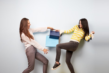 Two  girls dressed in nice stylish clothes are pulling each other bags after shopping on the white background