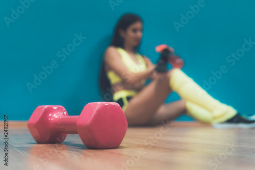 Close up of pink dumbbell lying on the gym floor at sitting