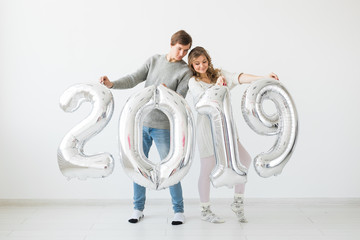 New 2019 Year is coming concept - Funny young man and woman are holding silver colored numbers on white background