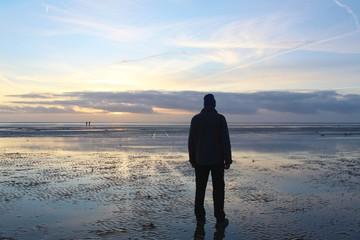Mann betrachtet den Sonnenuntergang am Wattenmeer, Nordseeinsel Fanö, Dänemark