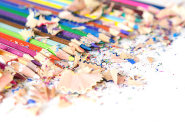 Drawing tools background. Lot of colorful pencils frame with sawdust and shavings on white.