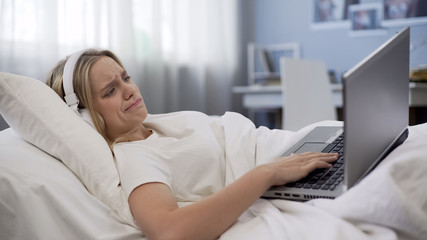 Upset woman lying in bed, disappointed with old laptop malfunction, service