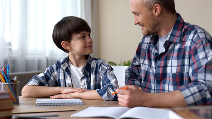 Male kid and father doing homework together, smiling to each other, teamwork