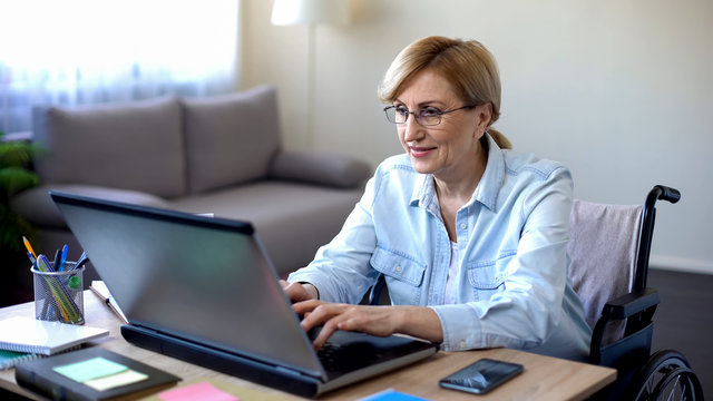 Successful senior woman in wheelchair working on laptop, chatting with client