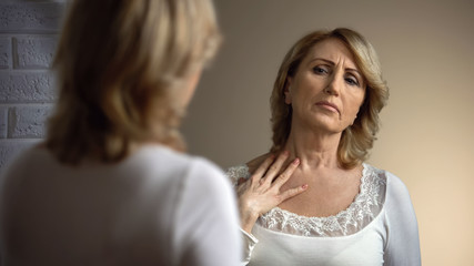 Unhappy senior woman looking in mirror and touching decollete zone, wrinkles