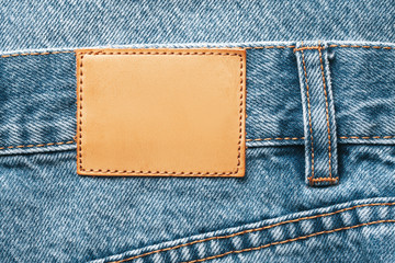Fashion detailed background with empty copy space fror graphic design. Brown, blank leather label tag. Blue jeans denim texture with thread sew lines.