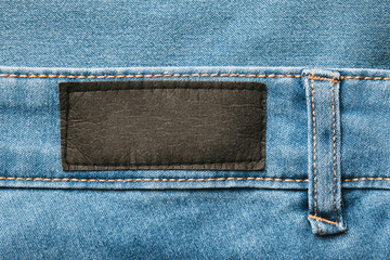 Empty copy space black label patch on blue jeans denim background.