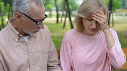 Elderly man supporting wife suffering headache, migraine symptom, health problem