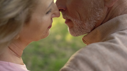 Aged husband and wife kissing closeup, love feeling, married couple togetherness