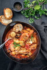 Traditional French Corsican fish stew with prawns, mussels and fish as top view in a modern design Japanese cast-iron roasting dish