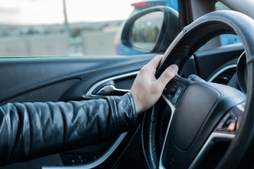 Male driver holding steering wheel while driving