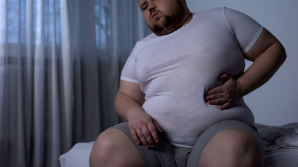 Big young man suffering from stomach pain, acid reflux, fat liver disease, diet