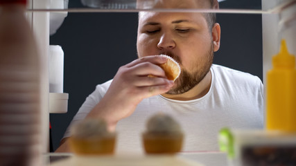 Overweight man delicious cupcake at night, diet failure, unhealthy lifestyle