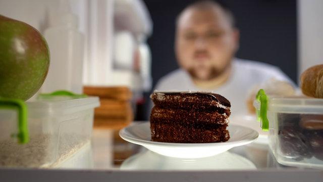 Oversize man taking piece of cake from fridge at night, diabetes risk, calories