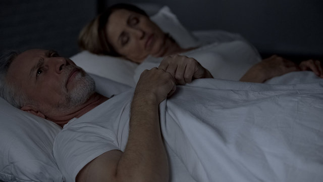 Senior man lying in bed having hard thoughts, unfaithful relations, troubles