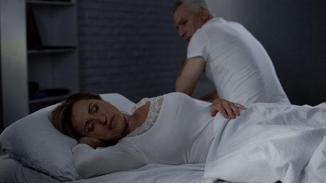 Senior man looking at sleeping wife, male sitting on far bed edge backwards