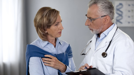 Aged physician talking to serious female patient, showing test results, medicine