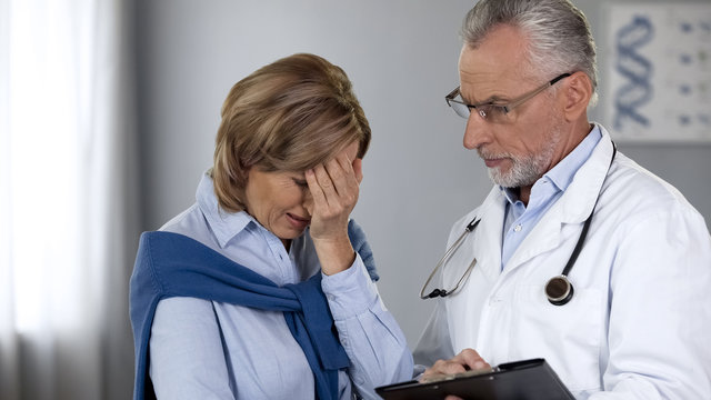 Oncologist informing upset lady about bad test results, cancer treatment