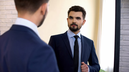 Businessman is suit looking in mirror before important meeting, checking outfit