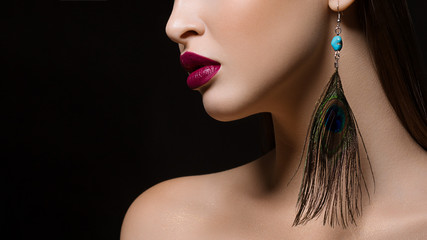 Close-up of the lower part of the face of a woman with perfect skin and plump, expressive lips the color of marsala. The image on an isolated black background adds glamor to the image.