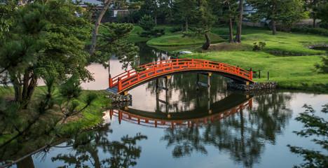 Orange japanese bridge in beautiful garden
