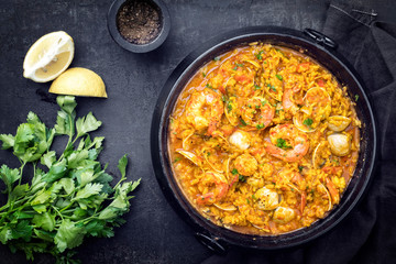 Traditional Portuguese arroz caldoso con almejas with shrimps and calm as top view in a cast-iron pot