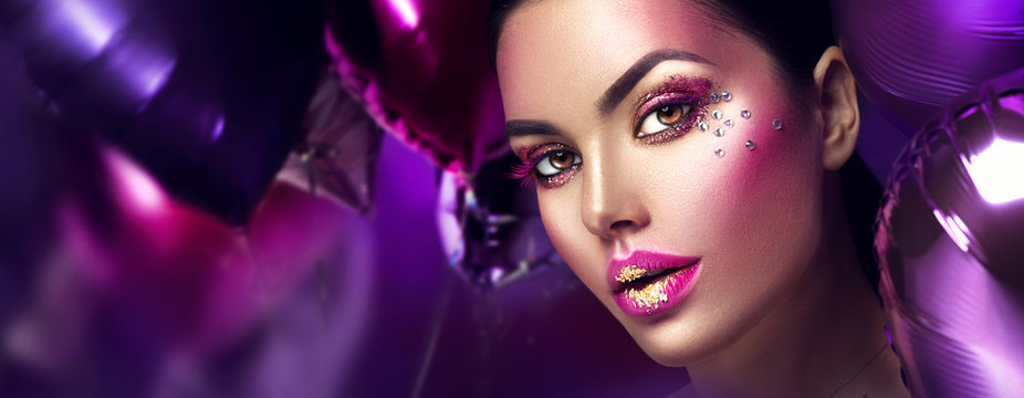Beauty fashion model girl creative art makeup with gems. Woman face over purple, pink and violet air balloons background