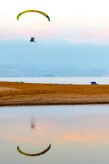 Atardecer junto al mar mientras la tarde cae y la gente pasea por la playa, pesca o contempla el paisaje