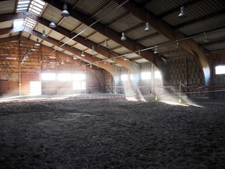 Empty indoor horse riding hall. View in an indoor riding arena. The riding school is suitable for dressage horses.